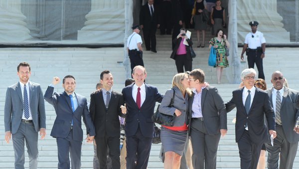 Plaintiffs Sandy Stier and Kristin Perry kiss on Wednesday (June 26) as they leave the Supreme Court with others who argued against California's Proposition 8, which banned gay marriage.  Two other plaintiffs, Jeff Zarrillo, second left, and Paul Katami, third left, exited with them. Between the couples is attorney David Boies. The high court rejected Prop 8 on legal grounds. RNS photo by Adelle M. Banks
