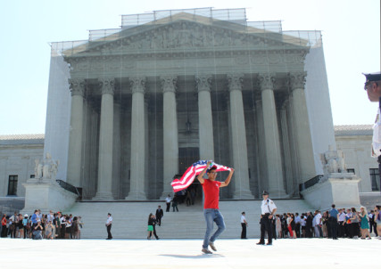 A man exits the Supreme Court building carrying an American flag after the high court made its rulings on same-sex marriage Wednesday (June 26, 2013). RNS photo by Adelle M. Banks