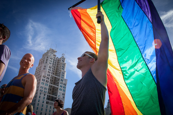 Wes Warner (right) holds a gay pride flag during a rally celebrating the Supreme Court's gay marriage ruling at Ilus W. Davis Park in Kansas City, Mo., on June 26, 2013. RNS photo by Sally Morrow