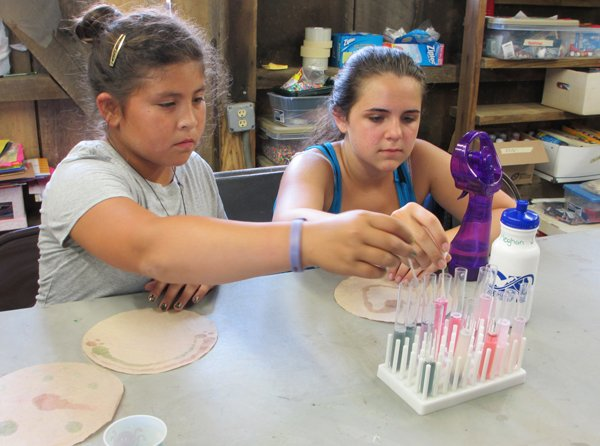 Campers Piper (left, no last name provided) and Meghan Judge (right) paint cabbage juice-soaked coffee filters with various liquidsduring a pH painting elective session at Camp Quest Chesapeake. RNS photo by Corrie Mitchell
