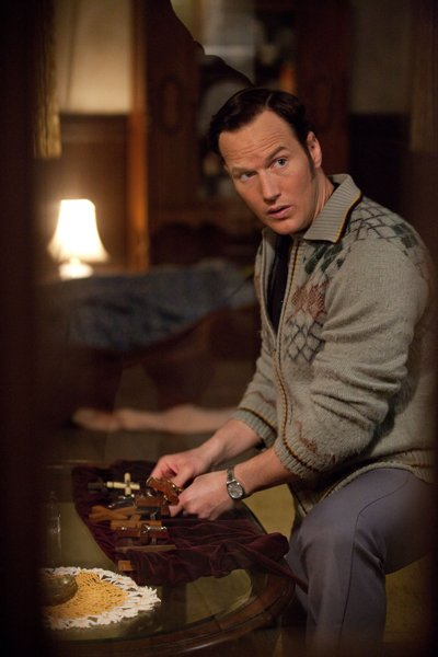 A scene from The Conjuring in which Ed (Patrick Wilson) sets crosses and holy water. Photo courtesy Grace Hill Media/Warner Brothers