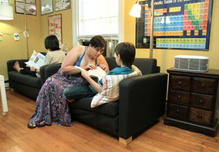 KellyAnne Kitchin and her son, Daniel, go over a lesson while oldest son Christopher, 12, reads in the background. The family's living room also serves as the main classroom. RNS photo by Rick Foster