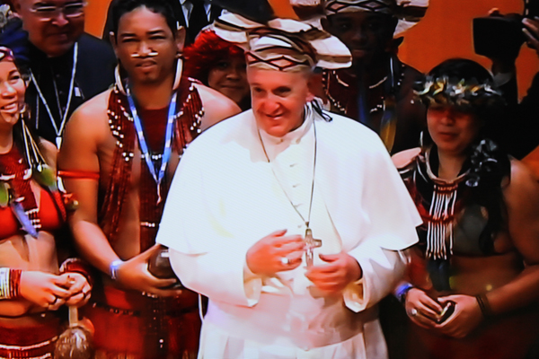 In one of the most inclusive gestures of his visit here, Pope Francis donned a headdress offered to him from an indigenous South American Indian at a ceremony in the city´s grand municipal theater. RNS photo by Robson Coehlo