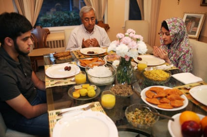Imran, 22, and his parents Habeeb and Seemi Ahmed pray in their Long Island, NY home just before breaking their fast after the first day of Ramadan on Aug. 11, 2010. RNS photo by Sally Morrow