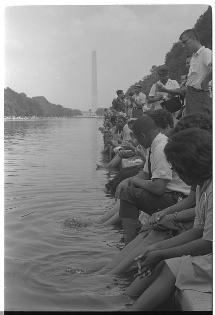 Demonstrators sit, with their feet in the Reflecting Pool, during the 1963 March on Washington. <a href=