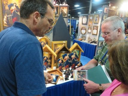"""Mike Nelson, left, of Nelson Fine Art & Gifts shows retailers the new """"Mary, Undoer of Knots"""" product line at the 17th annual trade show of the Catholic Marketing Network last week (Aug. 6-9) in Somerset, N.J. RNS photo by David Gibson."""
