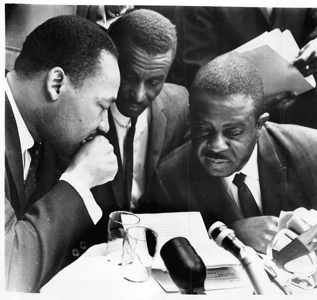"(May 10, 1963) The ""Big Three"" of the civil rights movement put their heads together here just before releasing a statement that accord had been reached on their grievances. (Left to right) The Rev. Martin Luther King, Jr.; the Rev. Fred Shuttleworth; the Rev. Ralph Abernathy. Religion News Service file photo"