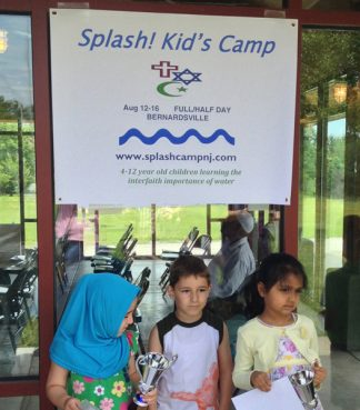 Children from Islamic Society of Basking Ridge stand under the sign for Spalsh! Kid's Camp. Photo courtesy Betsy LaVela