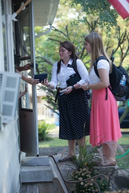 Sisters Ray (left) and Moody pass the Book of Mormon to a Kansas City, Mo., resident through her doorway while spreading their mission on Sept. 10, 2013. The sisters are carrying out their mission at the Church of Jesus Christ of Latter-day Saints' Independence Visitors' Center in Independence, Mo. RNS photo by Sally Morrow