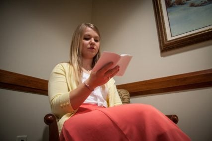 Sister Moody, from Elk Ridge, Utah, reads from the white handbook, which describes safety, health, exercise and other rules for missionaries, during companionship study at the Church of Jesus Christ of Latter-day Saints' Independence Visitors' Center in Independence, Mo. on Sept. 10, 2013. RNS photo by Sally Morrow
