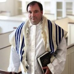 Rabbi Charles E. Savenor, director of congregational enrichment for the United Synagogue of Conservative Judaism, wears a prayer shawl (striped) over his kittel, a white shroud worn by some Jews during the High Holy Days of Rosh Hashana and Yom Kippur. Religion News Service photo by Michael Falco