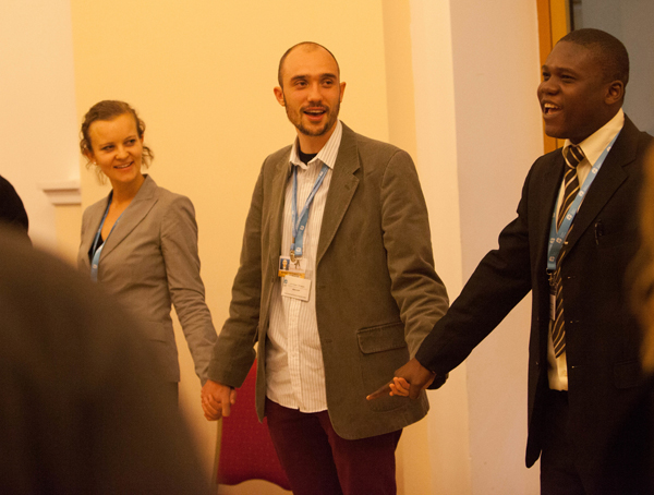 Left to right, Caroline Richter, Martin Kopp and Elija Zina hold hands during an Interfaith Youth discussion at COP19 in Warsaw. Photo courtesy of Sean Hawkey