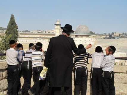 A group of ultra-Orthodox Jews in the Jewish Quarter of Jerusalem's Old City look out onto the Al-Aqsa Mosque on September 13, 2012. RNS photo by Neri Zilber