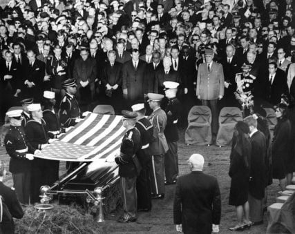 The burial and folding of the flag ceremony for President John F. Kennedy at his gravesite in Arlington National Cemetary, Washington, D.C. on November 25, 1963. Photograph includes: (right side, front to back) Jacqueline Kennedy, Robert F. Kennedy, Eunice Shriver, Patricia Lawford, Jean Smith, Super of the Arlington National Cemetary Jack Meltzer, (front row middle to right) President of West Germany Heinrich Luebbe, General Charles de Gaulle of France, Emperor of Ethiopia Haile Selassie, President of the Phillipines Diosdado Macapagal, and mourners. For use with RNS-JFK-ANNIV, transmitted on November 18, 2013, Photo by Abbie Rowe, National Parks Service, courtesy of John F. Kennedy Presidential Library and Museum, Boston