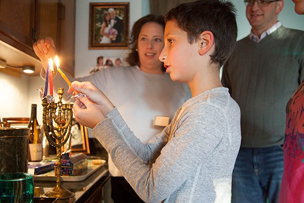 Quentin Wise lights a candle on the menorah for the second night of Hanukkah, also Thanksgiving, with his family in Leawood, Kan. on Thursday (Nov. 28). RNS photo by Sally Morrow