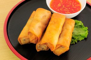 A photo of Chinese eggrolls and a dip.