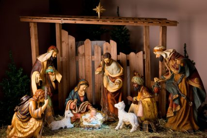A Christmas manger scene with figurines including Jesus, Mary, Joseph, sheep and magi.