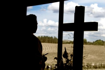 A member of clergy stands next to a cross looking out a window.
