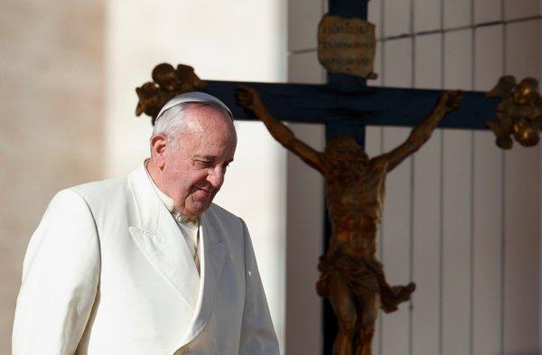 Pope Francis passes a crucifix as he walks down steps during his general audience in St. Peter's Square at the Vatican Dec. 4. Photo by Paul Haring, courtesy of Catholic New Service