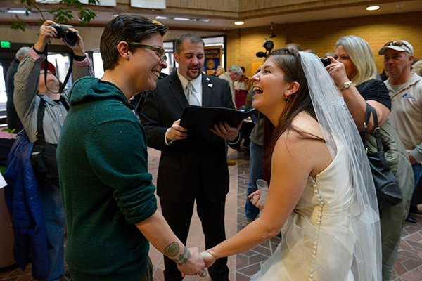 Jax Collins, left, and Heather Collins are overjoyed as they are married by Rev. Christopher Scuderi of Universal Heart Ministry on Monday (Dec. 23), at the Salt Lake City County offices. Hundreds of same-sex couples descended on county clerk offices around the state of Utah to request marriage licenses. A federal judge in Utah struck down the state's ban on same-sex marriage last Friday, saying the law violates the U.S. Constitution's guarantees of equal protection and due process. Photo by Francisco Kjolseth  |  The Salt Lake Tribune