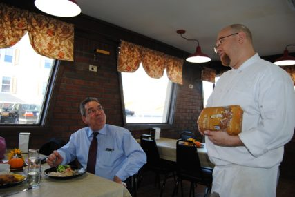 The Ark chef Matthew Blake, right, tells customer Michael Dubois about a bread made without oils. RNS photo by G. Jeffrey MacDonald