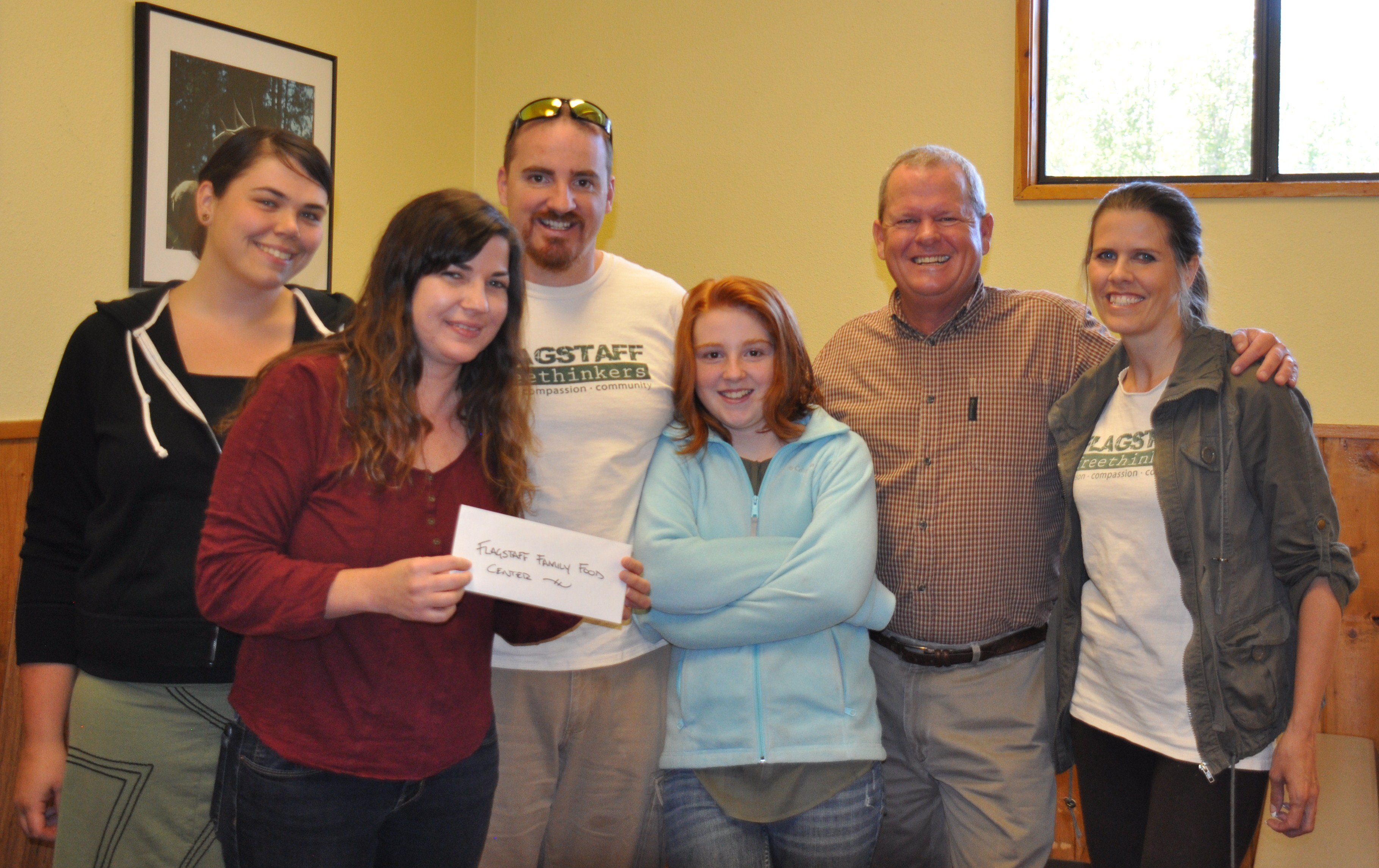 Members of the Flagstaff Freethinkers, including Brian Wallace, present money they raised for the Flagstaff Family Food Center last year.