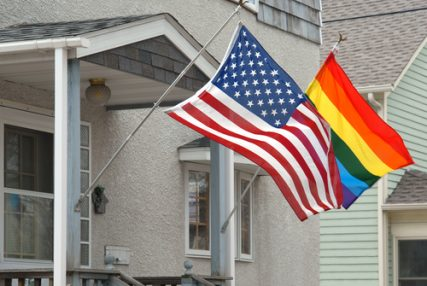 American and rainbow flag blowing in the wind on a suburban porch.