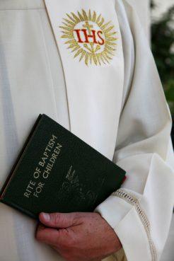 A priest prepares for a baptism.