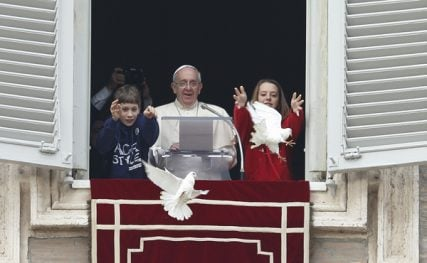 Pope Francis watches as children release doves from the window of his studio overlooking St. Peter's Square at the Vatican on Sunday (Jan. 26). The two young people at his side launched doves to highlight the church's call for peace in the world. Photo by Paul Haring, Catholic New Service