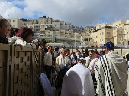 Women watching a bar mitvah from behind a wall next to the Western Wall in Jerusalem.