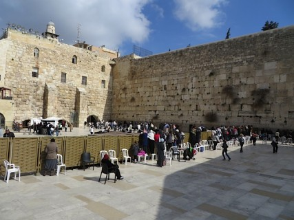 Women stand on plastic chairs and peer over a fence to watch their male relatives' bar mitzvahs near the Western Wall in Jeruslaem