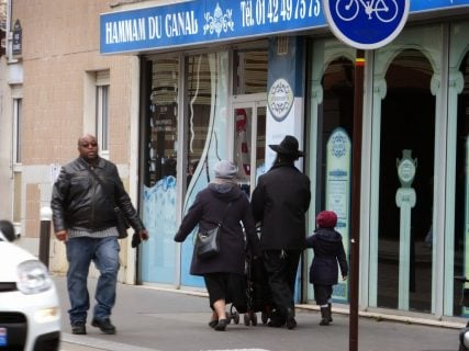 A Jewish family walks down a street in Paris' 19th arrondissement. RNS photo by Elizabeth Bryant