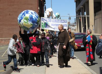 Rev. Sam Fuller, center, a Capuchin Franciscan priest from Middleton, Ct. leads a group of children on Earth Day 2013 during a march to bring awareness to climate change in Hartford. Photo courtesy of Patrick Watson