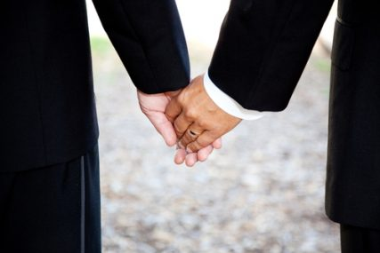Closeup of a same-sex couple holding hands, wearing a wedding ring.