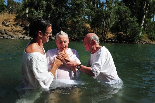 Two men prepare to dunk a third in a baptism rite in a river.