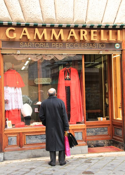 A passerby stops to look at the window display at Gammarelli tailor shop in Rome. Annibale Gammarelli and six generations of his family have dressed the popes since 1798, and their store is a historic landmark in the heart of Rome just behind the Pantheon. RNS photo by Josephine McKenna