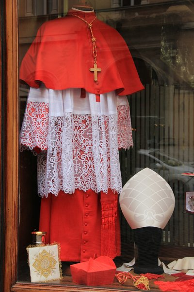 The shop window is ablaze with red as a mannequin displays the cardinals' ceremonial outfit at Gammarelli's tailor shop in Rome. RNS photo by Josephine McKenna