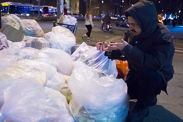 Gio Andollo looks for fruit among the trash bags outside Morton WIlliams Supermarket in New York. Photo by Esha Mahajan