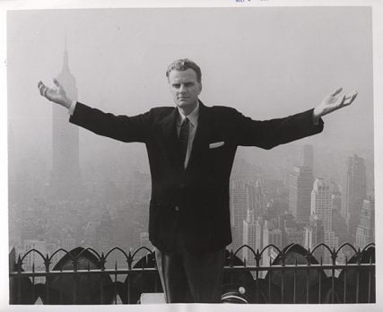 Evangelist Billy Graham stands on the rooftop of a skyscraper in New York City with the midtown skyline behind him to symbolize his New York crusade. Religion News Service file photo courtesy of Archives of the Billy Graham Center, Wheaton, Ill.