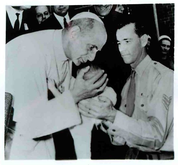 (1970) During a visit in Sydney, Pope Paul bends to kiss a baby held by his soldier father at the Royal Alexandra Hospital for Children in the Australian city. Religion News Service file photo
