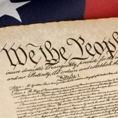 The U.S. Constitution with an american flag.