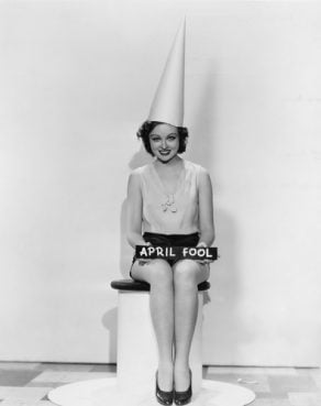 Portrait of woman with April Fool sign wearing dunce cap.