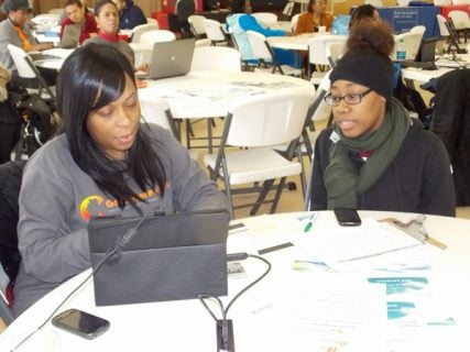 April Caldwell, right, age 19, successfully enrolls in Medicaid with help from Latonya Rover, left, an In-Person Counselor for Beloved Community Family Wellness Center, at a Get Covered America health care enrollment event at the Allen Metropolitan CME church in Illinois. Photo courtesy of Get Covered America