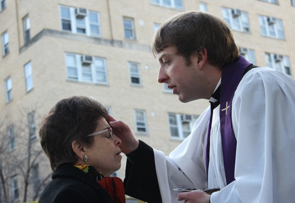 Mary Jo Binker of Rosslyn, Va. receives ashes from the Rev. Kyle Oliver, assistant priest at St. Paul's Parish in Washington, D.C., on Ash Wednesday (March 5, 2014) near the Foggy Bottom Metro station in Washington. RNS photo by Adelle M. Banks