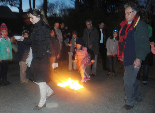 """Two dozen people huddled outside in 23-degree temperatures on Tuesday evening (March 18) in Watertown, Mass., to eat a traditional Iranian soup called """"ash"""" and jump over a line of several small fires as part of a 3,000-year-old Festival of Fire ritual rooted in Zoroastrianism. RNS photo by Omar Sacirbey"""