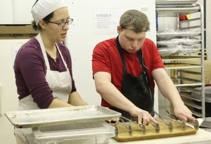 Jamie Emery, assistant to the chef at the Sunflower Bakery in Gaithersburg, Md., works with student Patrick O'Toole as he cuts blondies on March 7, 2014. RNS photo by Adelle M. Banks