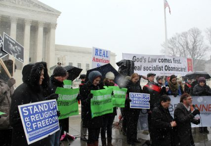 Supporters pray outside the Supreme Court as they support businesses challenging the contraception mandate of the Affordable Care Act on Tuesday (March 25). In the foreground far right, the Rev. Frank Pavone of Priests for Life, left, and the Rev. Patrick Mahoney, right, kneel in prayer during a vigil. RNS photo by Adelle M. Banks