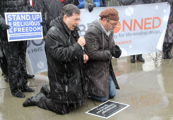 Rev. Frank Pavone of Priests for Life, left, leads a prayer beside Rev. Patrick Mahoney right, in front of the Supreme Court, as they support businesses challenging the contraception mandate of the Affordable Care Act on Tuesday (March 25). RNS photo by Adelle M. Banks