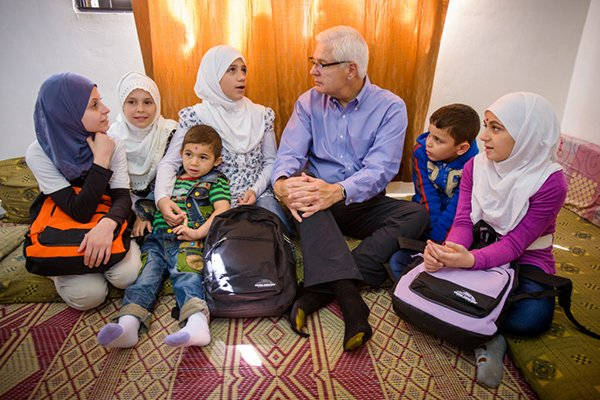 World Vision's U.S. President Rich Stearns, center, visits with Syrian refugees in Irbid, Jordan. Photo by Jon Warren, courtesy of World Vision