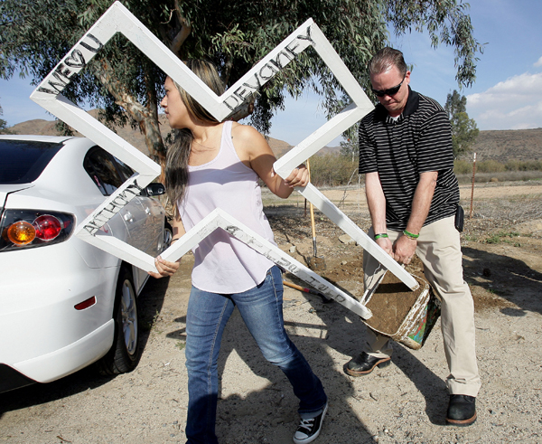 March 6, 2014 - Lake Elsinore, Ca - Mercedez Devaney, 24 and her father Chad Devaney remove one of the roadside memorial crosses for 19-year-old Anthony Devaney after pressure to take down the crosses from the American Humanist Association on Lake St. and Temescal Canyon Road in Lake Elsinore, on March 06. Photo courtesy of © Frank Bellino/Press Enterprise/ZUMAPRESS.com
